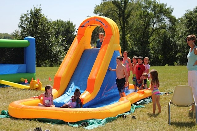 Bouncy slide at a fall kickoff with children and water.