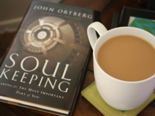 Soul Keeping book on a table next to a cup of coffee